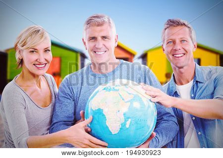 Portrait of people holding globe  against multi colored huts on sand against clear sky