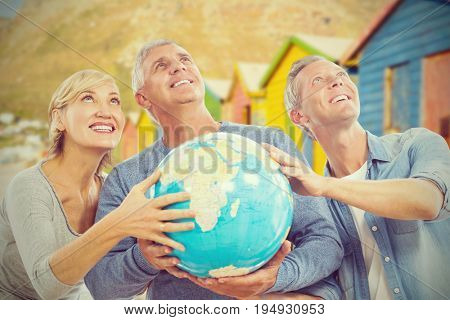 Smiling people looking up while holding globe against multi colored beach huts on sand
