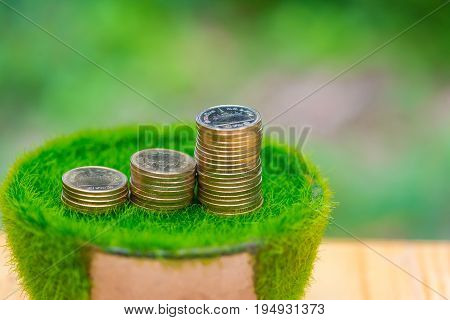 Stack Of Gold Coin On Artificial Grass In Pot, On Wooden Table With Green Nature Background.