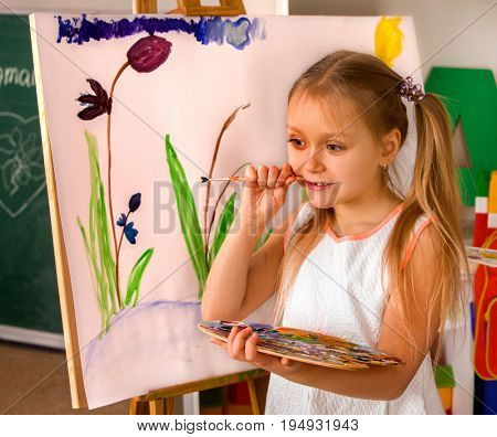 Child painting on easel. Girl learn paint in class school. Kid gnawing brush. Children's picture on background.