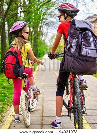 Bicycle path with children. Girls wearing bicycle helmet with rucksack ciclyng ride. Kids are on yellow bike lane. Alternative to urban transport . Oldest girl teaches younger rules of road.
