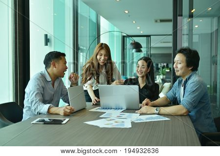 Teamwork of Asian business people succeed a project tag team