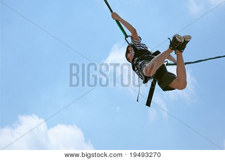 Bungee Jumping Boy Against Blue Cloud Sky With Clipping Path