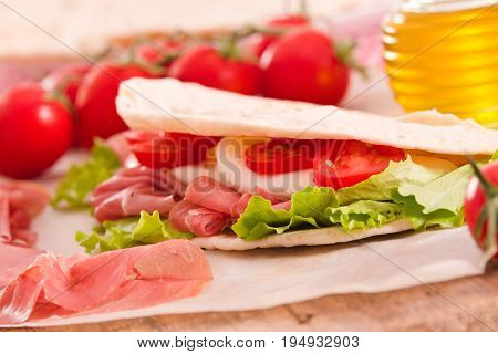 Piadina with ham and lettuce on wooden table.