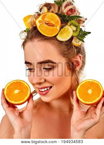 Hair mask from fresh fruits on woman head. Girl with beautiful face holds halves of orange for homemade organic skin and hair therapy. Concept of hydrating healthy and beauty hair and skin. Female not poster