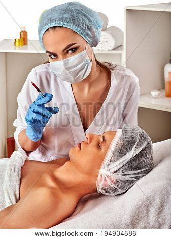 Filler injection for male forehead face. Plastic aesthetic facial surgery in beauty clinic. Man giving anti-aging injections. Doctor in medical gloves with syringe injects nasolabial fold drug