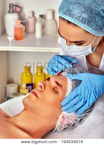 Filler injection for male forehead face. Plastic aesthetic facial surgery beauty clinic. Man giving anti-aging procedure. Doctor in medical gloves with syringe injects. Expensive skincare injections.
