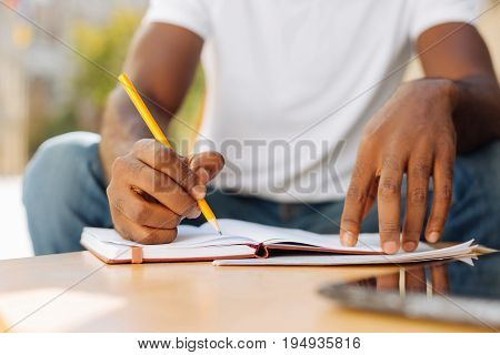 Better note it. Young smart charismatic guy writing a tip reminding himself of an errand while working on a plan for the day