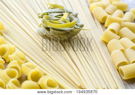 One piece of green raw pasta is on the yellow linguini