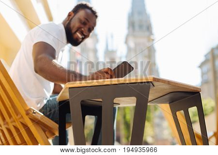Instant texting. Handsome industrious capable guy sitting on a terrace outdoors and enjoying sunny day while receiving a message from friend