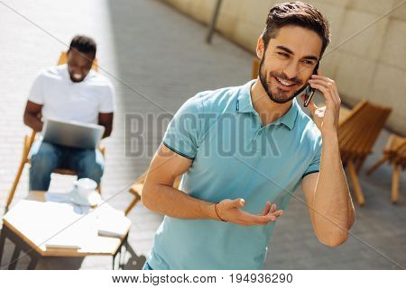 Give me a favor. Persuasive strategic smart guy making a phone call and inviting his colleague for a meeting while working on some business idea