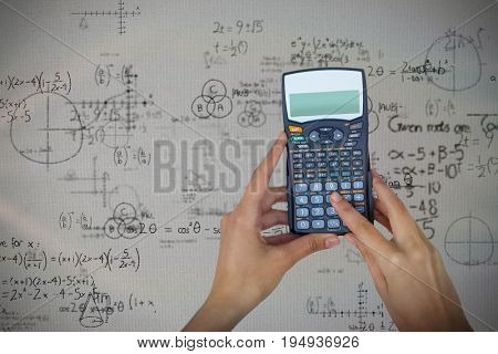 Cropped hands of businesswoman using calculator against mathematical problems with diagrams and solution