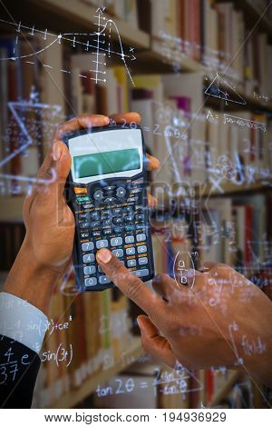 Hands of businessman using calculator  against maths problems solved on blackboard