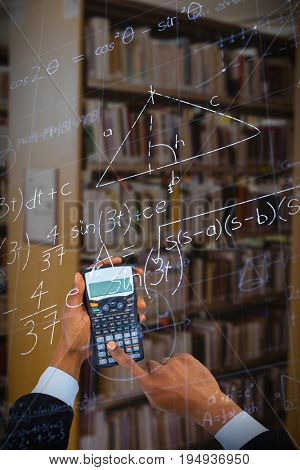 Cropped hands of businessman using calculator  against low angle view of mathematical equations with solution