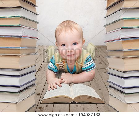Little baby reads a book in a pile of books