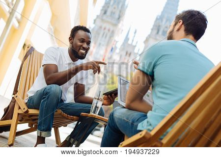 Eager for success. Capable productive enterprising man meeting with his friend and discussing their common project while sharing his opinion