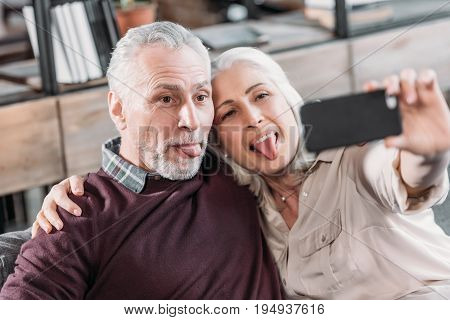 Grimace Senior Couple Sticking Tongue Out And Taking Selfie While Resting On Sofa At Home