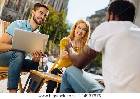 Informal interview. Lively talented ambitious guy sitting on a terrace and talking to his friends who stating new venture and looking for employees