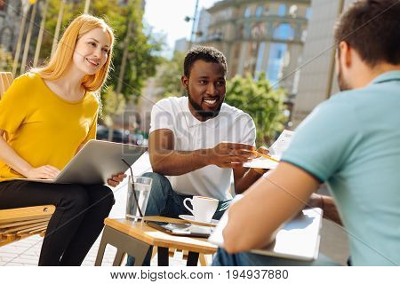 You got the job. Two remarkable industrious daring people asking his friend joining the team and granting him official employment while discussing it informally in a cafe