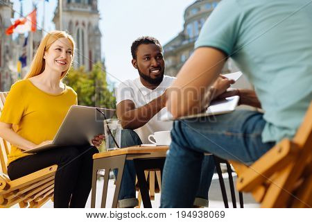 Progressive thinking. Lively passionate enterprising people gathering in a cafe for discussing their startup and working informally