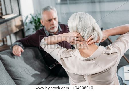 back view of senior woman suffering from strong neck ache