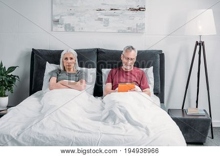 Man Using Tablet While Grumpy Wife Lying In Bed Near By