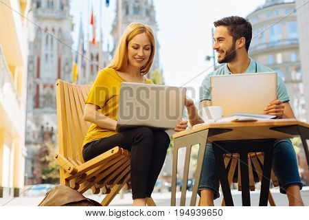 Big city enterprise. Two industrious ambitious young people meeting on a terrace and working on their startup concept while sharing their opinions