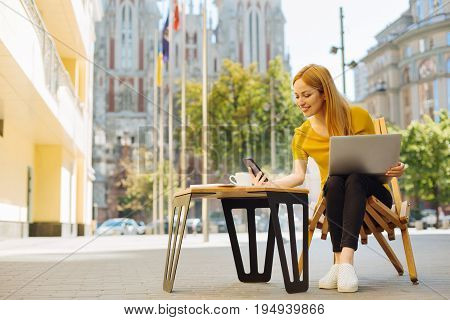 Workplace in a big city. Vibrant sociable clever woman taking her smartphone and reading a message while working on a terrace