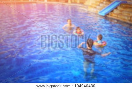 Blurred swimming pool actvity; Asian fathers taking care and teaching their kids to swim; add flare light - Copy space for text on the left.