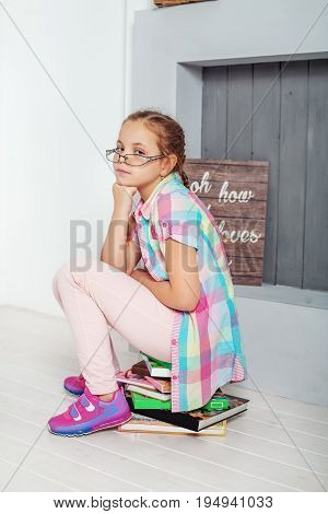 The child is sitting on book in glasses. The concept of education and childhood.