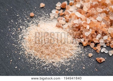 fine and coarse crystals of pink  Himalayan salt on gray slate stone