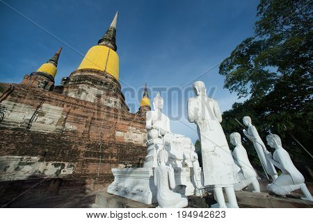 AYUTTHAYA,THAILAND-JULY 9,2017 : Group of Buddha statues and ruined at Principal Chedi in Wat Yai Chai Mongkhon the Great Monastery of Auspicious Victory is located Ayutthaya Historical Park in Ayutthaya old capital city in Middle of Thailand.
