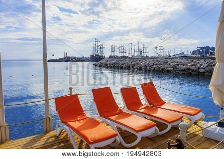 A view of sun loungers amid sailboats in the town of Kemer.