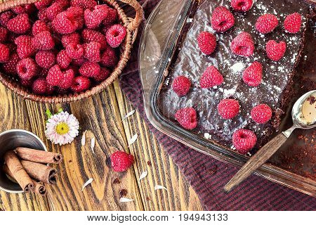 Homemade traditional sweet delicious dark chocolate brownies pie tart cake with chocolate glaze raspberries fruit green mint leaves rustic wooden table background top view baked in glass jar close up