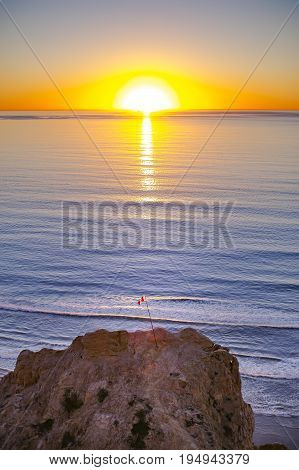 A flag sits atop a large rock with the sunset behind it