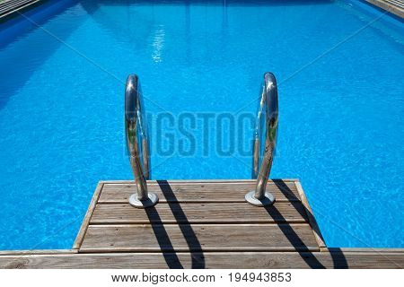 Railing stairs down to the pool with clean blue water