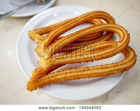 Close-up churros or Spanish fried-dough pastry on white plate .