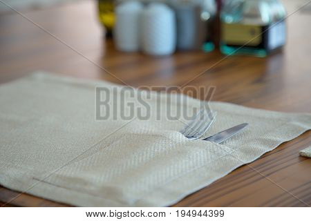 Fork and knife in napkin on a wooden table