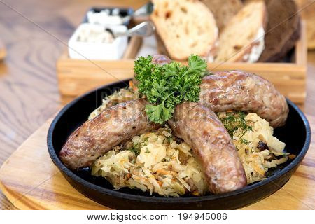 Sauerkraut with home-made sausage on a frying pan