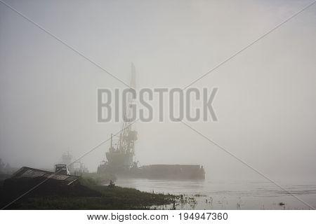 floating crane barge derrick in fog on river