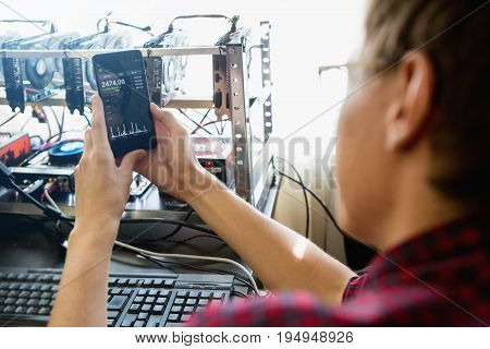 Man with a phone. On the screen bitcoin exchange rate. Mining computer on a background.