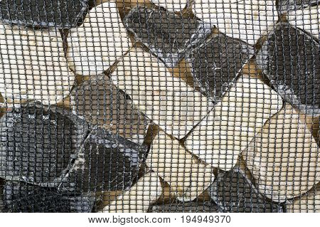 Tile from dolomite stones on a grid on a wooden background