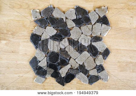 Tile from dolomite stones on a grid is isolated on a wooden background
