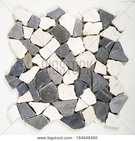 Tile from dolomite stones on a grid is isolated on a white background