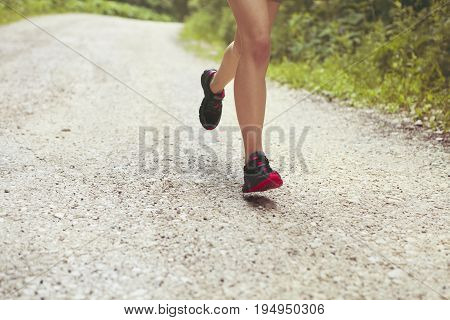 Young fitness woman runner athlete running at country road