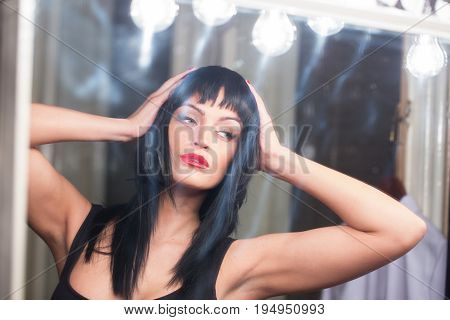 Young woman trying fit black wig in mirror
