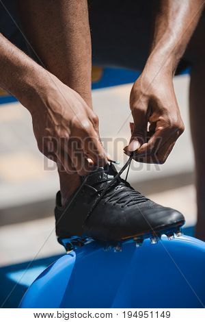 Cropped Shot Of Man Tying Shoelaces While Sitting On Stadium