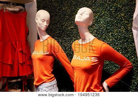 Two female dummies in clothes with the inscription: Sales. Orihuela, La Zenia. Spain.