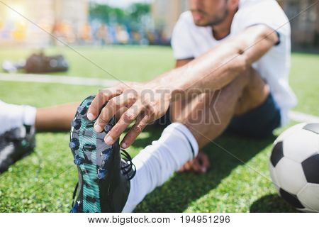 Selective Focus Of Soccer Player Holding Football Boot While Sitting On Pitch
