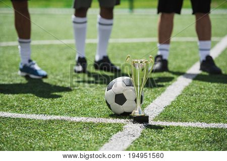 Goblet And Soccer Ball On Football Field With Players Standing Behind